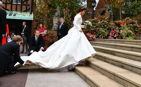 Eugenie climbs the steps of the church with help from two aides who are holding the train of her Peter Pilotto designed dress